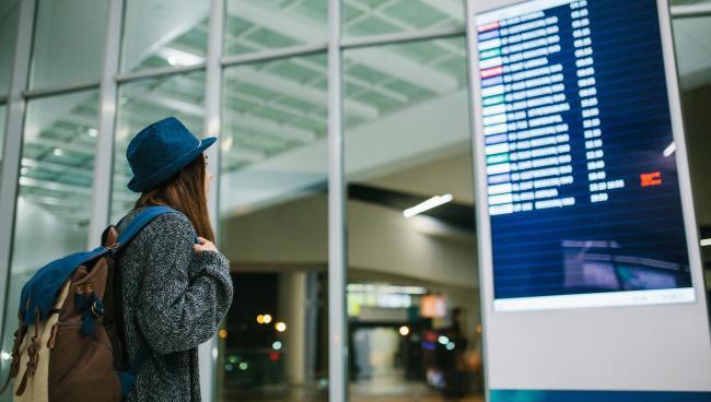 Девушка в аэропорту стоит перед таблом вылета